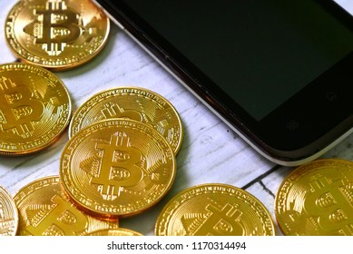 Cryptocurrency theme. Golden bitcoin replica with mobile phone. Business and finance concept.