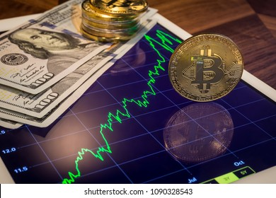 Cryptocurrency and US 100 dollar banknotes, focus gold Bitcoin reflect on tablet screen show green price stock market trend graph. Concepts of transfer or exchange digital money through blockchain.