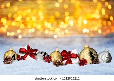 Cryptocurrency xmas background crypto coin christmas bauble balls and gifts in snow in front of warm lights bokeh snow texture