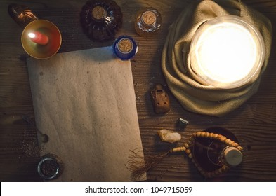 Crystal ball and ancient magic blank scroll page with copy space on fortune teller magic desk table background. Seance concept.