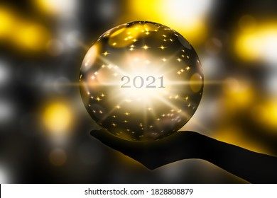 crystal ball in a hand, prediction for new year 2021 on abstract shiny blurred background