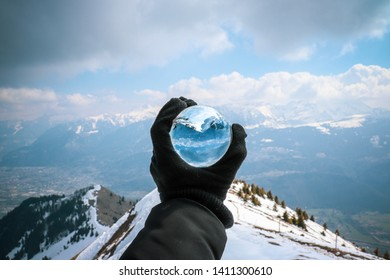 Crystal ball held in one hand at the top of a mountain