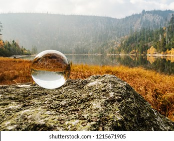 Crystal ball at the lake. Mirroring in a ball of the lake wall at the Lake of Ball in the Sumava National Park in autumn. Czech Republic