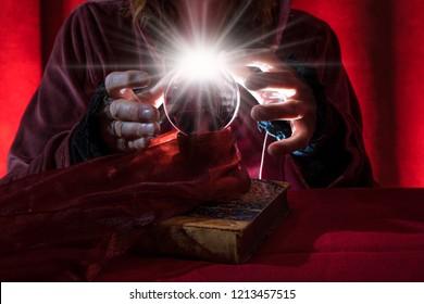 a crystal ball lies between the hands of a fortune teller