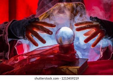 A crystal ball lies between the hands of a fortune teller, fog rises.