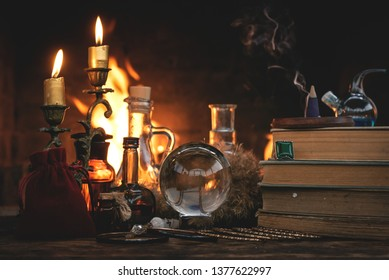 Crystal ball, magic book, magic potion and other wizard accessories on a table on a burning fire background.