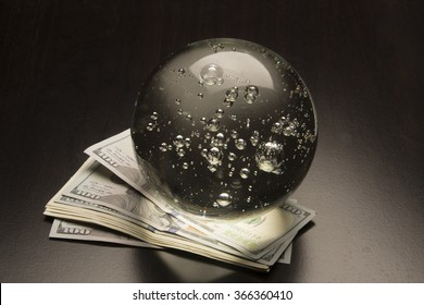 Crystal ball and money/Economy Prediction/Glass globe sits on a pile of cash