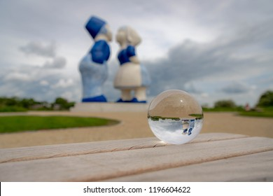 A crystal ball on the wooden table with with Kissing Couple XXXL as background, Amsterdam, Netherlands.