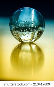 A crystal ball on a yellow table.