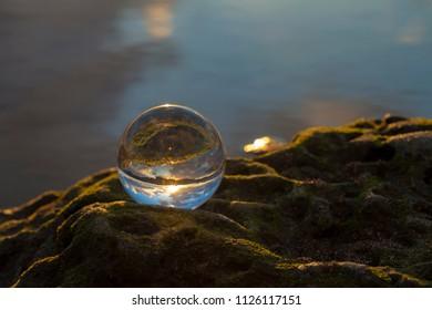 Crystal ball photography - sunset beach, ball on a rock