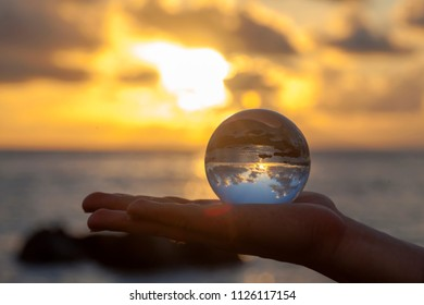 Crystal ball photography - sunset beach, hand holding the ball