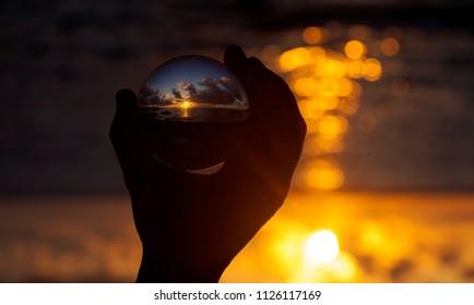 Crystal ball photography - sunset beach, hand holding the ball