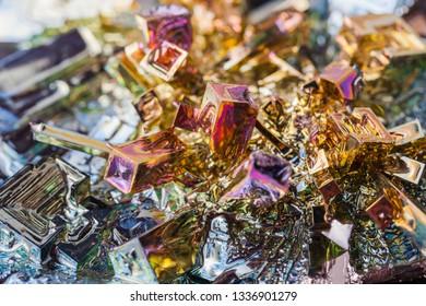 Crystal of bismuth on dark stone background