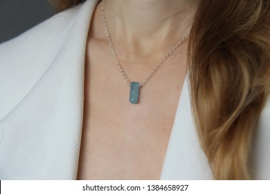Crystal blue aquamarine beryl on a silver chain on the girl. Pendant aquamarine, pendant, decoration on the neck. Natural blue aquamarine. Minimalism, Zen. Copy space for your text.