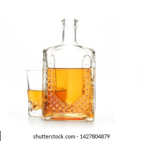 A crystal carafe and a glass of whiskey on a white background