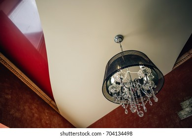 Crystal chandelier with a black lamp shade under a stretch ceiling. An interior of Artdeco.