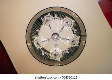 Crystal chandelier with a black lamp shade under a stretch ceiling - top view, bottom view. An interior of Artdeco.