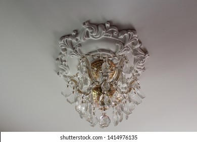 Crystal chandelier with a gold fixture and a white molded ceiling medallion on a white ceiling.