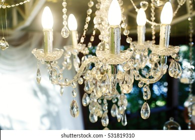 Crystal chandelier hangs from the ceiling on porch