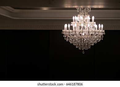 crystal chandelier shines hanging from the ceiling in the room