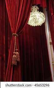 Crystal chandelier with theater stage red curtains