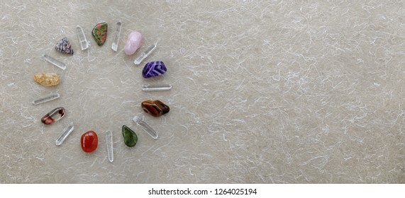 Crystal Circle Website Header - nine quartz wands and nine different tumbled crystals making a neat circular border against handmade beige paper with copy space on right