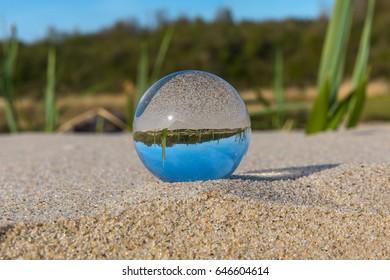 Crystal clear ball on the sandy beach