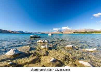 Crystal clear fresh glacier water at the pristine Lake Tekapo. Peaceful and calm mountain landscape, Mackenzie Basin, Canterbury, New Zealand.