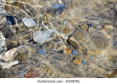 crystal clear lake tahoe reveals pebbles in the water as it ebbs and flows with sunlight creating interesting patterns