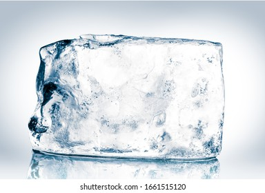 Crystal clear natural ice block in cold blue tones on reflective surface. Clipping path included.