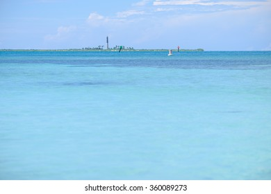 The crystal clear and shallow waters on the islands of the tropical Dry tortugas with the Loggerhead key lighthouse in the background on a separate island