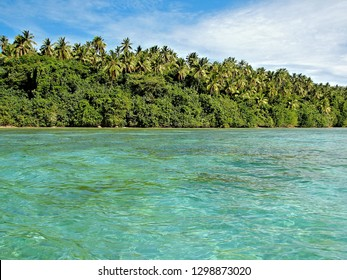 Crystal clear South Pacific water in the lagoon surrounding these tropical islands filled with coconut palm trees and healthy foliage