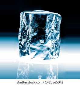 Crystal clear transparent shiny ice block, isolated on black background.