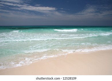 Crystal clear turquoise ocean waves crushing on a sandy beach. Isla Cozumel. Mexico