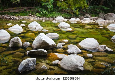 Crystal clear water flows around white boulders in the Mossman river world heritage tropical rainforest of North Queensland Australia.