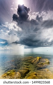 crystal clear water with green mossy stones at Lake Malawi, dark stormy clouds in the sky, Africa