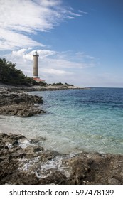 Crystal clear water on the beach with lighthouse by the sea on island Dugi Otok, Croatia