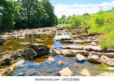 The crystal clear water of the rock strewn River Ribble on a summer day near Stainforth in the Yorkshire Dales