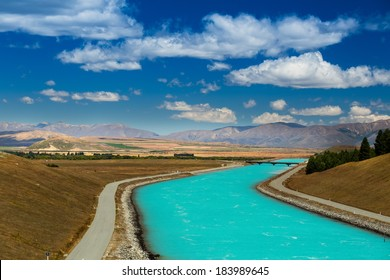 crystal clear water supply channel for the country drinking and industrial water needs. Background blue sky with clouds. In the background, mountains, forests and fields. New Zealand.