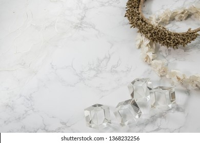 Crystal cubes and flower head band on white marble background.Flay lay image with empty space for montage work