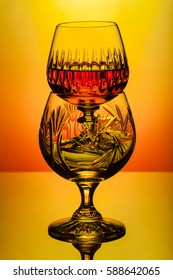 Crystal decanter and glasses with rum, carafe with whiskey on a glass table, colorful background