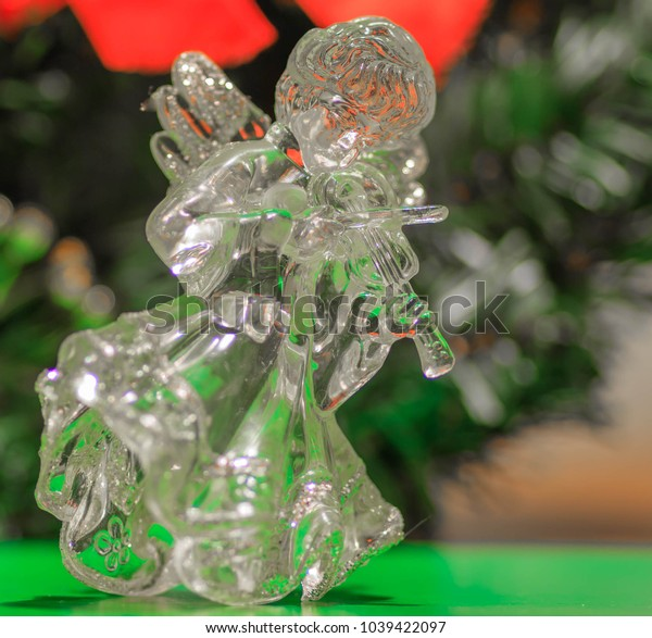 Crystal festive angel with a violin with a background from a New Year tree