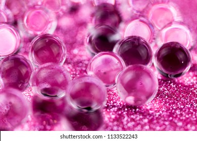 Crystal Gel water balls on pink glitter texture rotation. Close up macro footage.