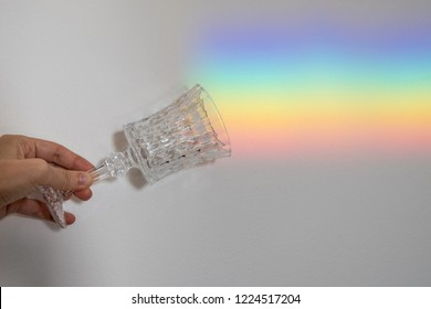 Crystal glass casts shadows and reflections under the light refracted into a rainbow