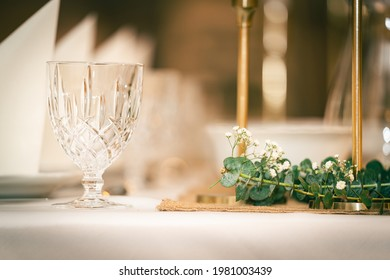 Crystal glass with eucalyptus on dinner table with Dekoration and candles