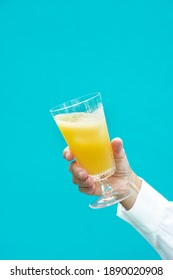 crystal glass of orange juice in man hand