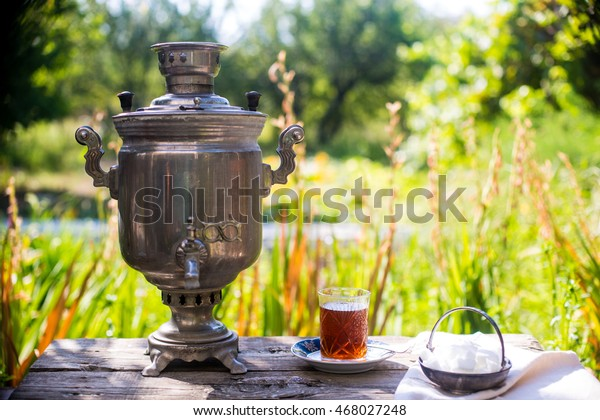 Crystal glass of tea on blue saucer with metal samovar and sugar cubes vintage bowl