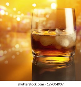 crystal glass with whiskey on a glass table