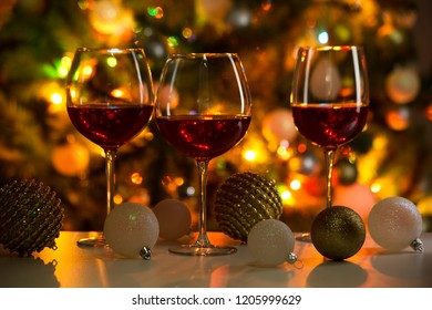 Crystal glasses of wine and Christmas balls on the background of Christmas lights