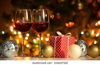 Crystal glasses of wine and Christmas balls and Christmas gifts on the background of Christmas lights
